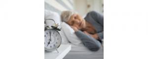 senior citizen sleeping with an alarm clock set