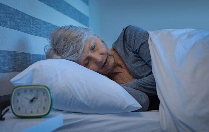 older lady sleeping with alarm clock