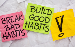 one sticky note that says bread bad habits, another that says build good habits and one that has an explanation point